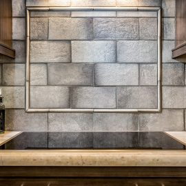 Lakeside Rebuild – The backsplash is a handmade stamped concrete tile with a great pattern on it. It creates depth and variation adding interest to the space